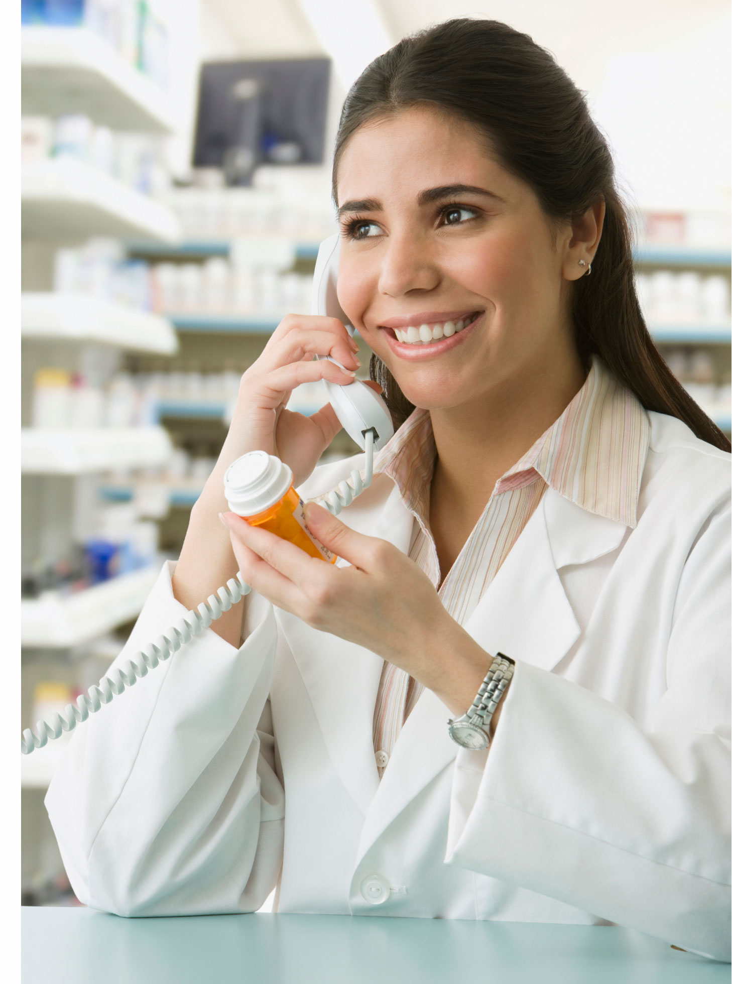 pharmacy tech holding a pill bottle while talking on the phone - Cvs Pharmacy Technician Job