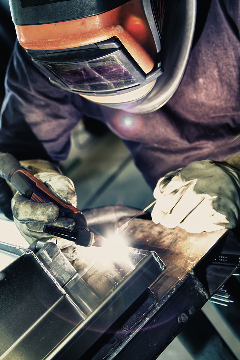 Technician welding on a piece of equipment