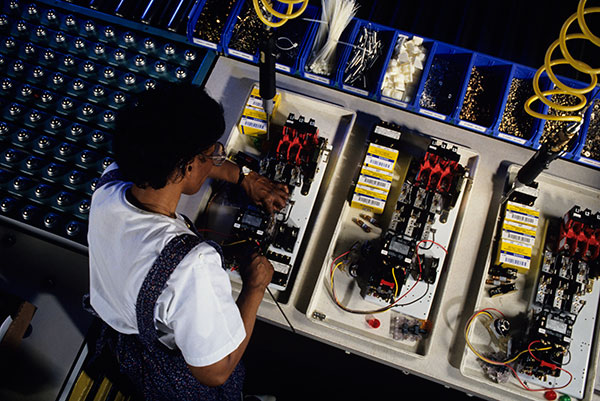 A techniciam working on a circuit board